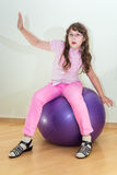 Young little girl sitting on big ball Royalty Free Stock Photo