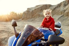 Young little girl sitting on a motorcycle racing, beautiful little biker on a sports bike in nature. The daughter of a motorcycle stock photography