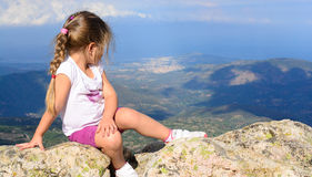 Young little girl sitting on to the rock Royalty Free Stock Images