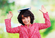 Young little girl standing with notebook on head Royalty Free Stock Photos
