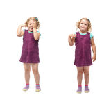 Young little girl standing over isolated white background. Young indignant little girl with curly hair in purple dress standing over isolated white background Royalty Free Stock Image