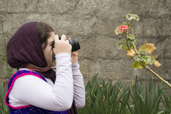 Young Little Girl Is Taking Photograph by an Analogue Camera Str. Apped on Her Neck in Flower Garden Royalty Free Stock Image