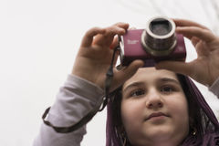 Young Little Girl Is Taking Photograph by Point and Shoot Camera Royalty Free Stock Images