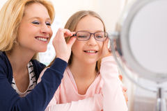 Young little girl trying glasses at the optician w her mother Royalty Free Stock Photos