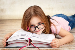 Young little girl wearing glasses and reading a book Stock Images