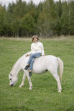 Young little girl in a white sweater and jeans sitting cross-legged on a white horse. Lifestyle portrait stock images