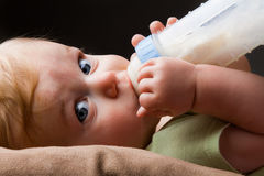 Young little guy drinking his bottle Royalty Free Stock Image