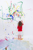Young Little Kid Painting on White Big Wall Royalty Free Stock Images