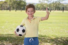 Young little kid 7 or 8 years old enjoying happy playing football soccer at grass city park field posing smiling proud standing ho. Lding the ball in childhood Stock Images