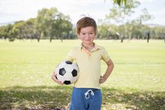 Young little kid 7 or 8 years old enjoying happy playing football soccer at grass city park field posing smiling proud standing ho. Lding the ball in childhood Royalty Free Stock Photos