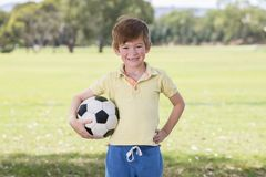 Young little kid 7 or 8 years old enjoying happy playing football soccer at grass city park field posing smiling proud standing ho stock photography