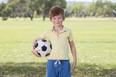 Young little kid 7 or 8 years old enjoying happy playing football soccer at grass city park field posing smiling proud standing ho. Lding the ball in childhood stock photos