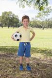 Young little kid 7 or 8 years old enjoying happy playing football soccer at grass city park field posing smiling proud standing ho. Lding the ball in childhood royalty free stock photography
