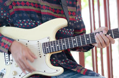 Young Living and practicing electric guitar happily at home. Stock Photography