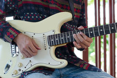 Young Living and practicing electric guitar happily at home. Royalty Free Stock Photography