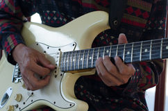Young Living and practicing electric guitar happily at home. Royalty Free Stock Photos