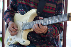 Young Living and practicing electric guitar happily at home. Royalty Free Stock Image