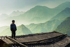 Young local boy standing at the rooftop overlooking the mountains Royalty Free Stock Image