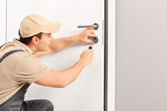 Young locksmith installing a lock on a door. Young male locksmith installing a lock on a new door with a screwdriver stock images
