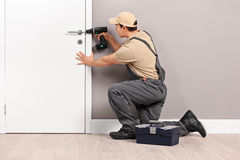 Young locksmith installing a lock on a door. Young male locksmith installing a lock on a new white door with a hand drill stock images