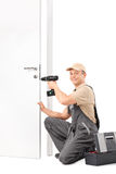Young locksmith screwing a lock on a door. Vertical shot of a young locksmith screwing a lock on a door with a hand drill and looking at the camera isolated on royalty free stock photo
