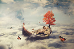 Young lonely beautiful woman drifting on a boat above clouds. Dreamy screensaver. With skyline background Stock Photography