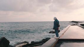 Young lonely girl standing at pier at rain. Lonesome girl looking at stormy sea. Woman stands at deserted promenade. Sad beautiful stock footage