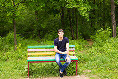 Young lonely man sitting on a bench waiting for something. Stock Images