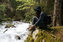 Young lonely tourist cutie girl sitting on stone on shore of river in mountains in wild terrain and satisfying thirst. Drinking water from glass Stock Image