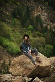 Young lonely tourist cutie girl sitting on stone on shore of river in mountains in wild terrain and satisfying thirst. Drinking water from glass Royalty Free Stock Photography