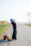 Young lonely woman and baby on roadside with Royalty Free Stock Photo