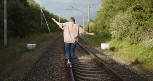 Young lonely woman walks along railroad track balancing on a rail