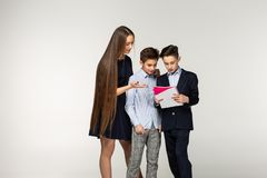 Young long haird sister in black dress helps younger brothers stock images