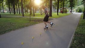 Young long-haired bearded man roller skater is dancing between cones in a nice evening in a city park. Freestyle slalom. Young man slalom skater is dancing stock footage