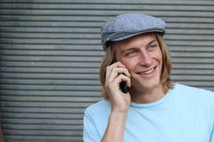 Young long haired blond man smiling and talking on mobile phone outside with copy space on the left.  Stock Photography