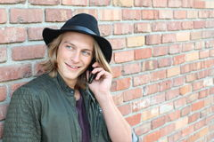 Young long haired blond man smiling and talking on mobile phone outside with space for copy.  Stock Photo