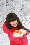 Young long-haired brunette with tangerines in hands. In a winter forest Stock Photo