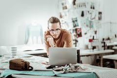 Young long-haired designer from a fashion school working on a new concept. New ideas. Young long-haired designer from a fashion school looking concentrated while royalty free stock images