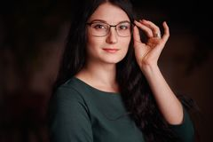 Young long-haired woman in glasses holds glasses. Young long-haired european woman with glasses looks into the camera and holds glasses with her hand. Bust stock image