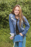 Young long haired girl in denim jacket outdoors in the village. Stock Photo