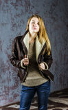Young long-haired girl in a leather jacket with  fur collar and jeans Stock Photos