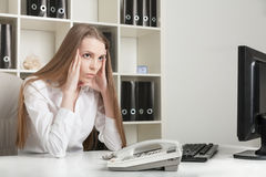 The young long-haired girl sits tired at office in the afternoon Stock Images