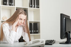 The young long-haired girl sits tired at office in the afternoon Stock Photography