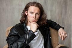 Young long-haired hunk with bristle in imposingly pose. Close-up portrait of young long-haired guy with bristle in white t-shirt and leather jacket imposingly royalty free stock photography