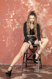 Young long-haired long-legged skinny girl in a black sweater and leather shorts and platform sandals Royalty Free Stock Image