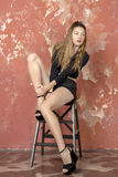 Young long-haired long-legged skinny girl in a black sweater and leather shorts and platform sandals Stock Photo