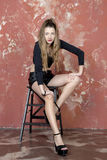 Young long-haired long-legged skinny girl in a black sweater and leather shorts and platform sandals Stock Images