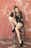 Young long-haired long-legged skinny girl in a black sweater and leather shorts and platform sandals Royalty Free Stock Images