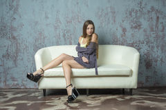 Young long-haired long-legged skinny girl in a sweater mini skirt and platform sandals Royalty Free Stock Photos