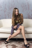 Young long-haired long-legged skinny girl in a sweater mini skirt and platform sandals Stock Photo
